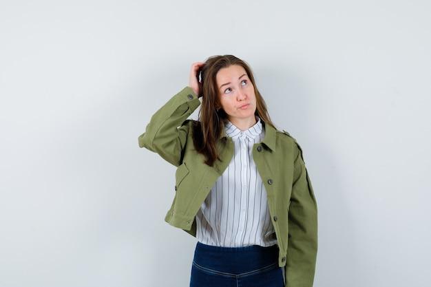 Jonge dame die hoofd krabt in shirt, jas en peinzend kijkt, vooraanzicht.