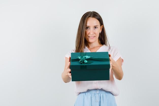 Jonge dame die huidige doos houdt en in t-shirt, rok, vooraanzicht glimlacht.