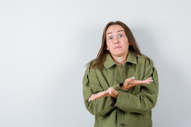 Jonge dame die hulpeloos gebaar in groene jas toont en er geen idee van heeft, vooraanzicht.