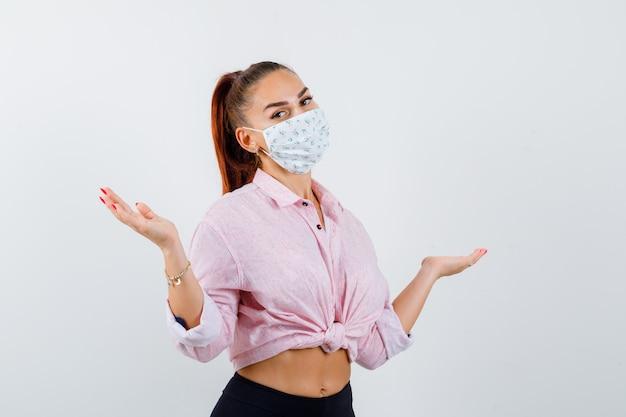 Jonge dame die hulpeloos gebaar in overhemd, broek, masker toont en verbaasd kijkt