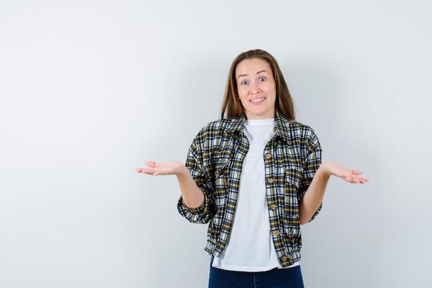 Jonge dame die hulpeloos gebaar in t-shirt, jasje, jeans toont en vrolijk, vooraanzicht kijkt.
