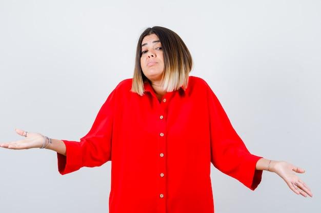 Jonge dame die hulpeloos gebaar toont in een rood oversized shirt en besluiteloos kijkt, vooraanzicht.