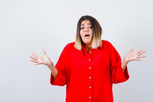 Jonge dame die hulpeloos gebaar toont in een rood oversized shirt en er angstig uitziet. vooraanzicht.