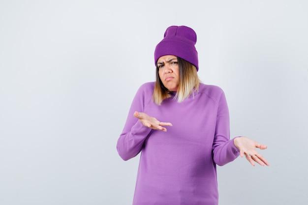 Jonge dame die hulpeloos gebaar toont in paarse trui, muts en ontevreden kijkt, vooraanzicht.