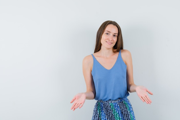 Jonge dame die idk-gebaar in blouse, rok, vooraanzicht toont.