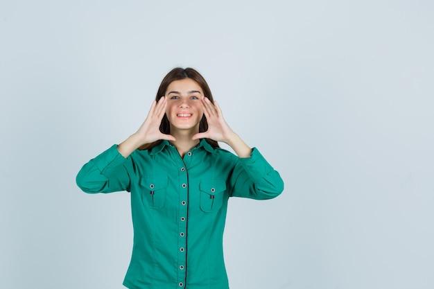 Jonge dame die iets aankondigt of geheim in groen overhemd vertelt en vrolijk, vooraanzicht kijkt.