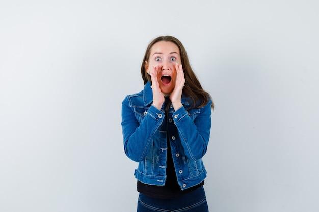 Jonge dame die iets in blouse schreeuwt of aankondigt en er gelukkig uitziet, vooraanzicht.