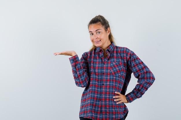 Jonge dame die iets in geruit overhemd presenteert en vrolijk kijkt. vooraanzicht.
