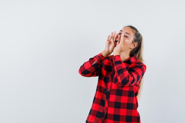 Jonge dame die iets in geruit overhemd schreeuwt of aankondigt