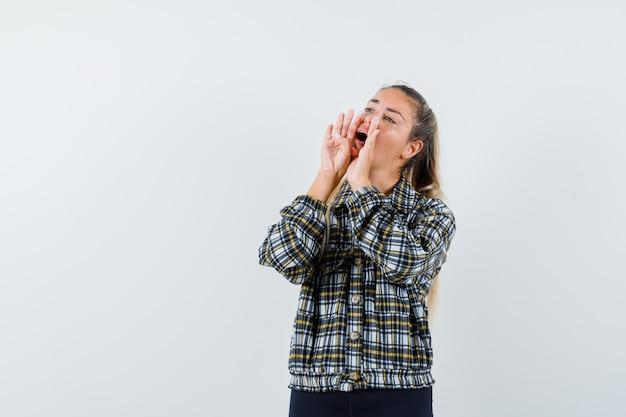 Jonge dame die iets in het vooraanzicht van het geruite overhemd schreeuwt of aankondigt.