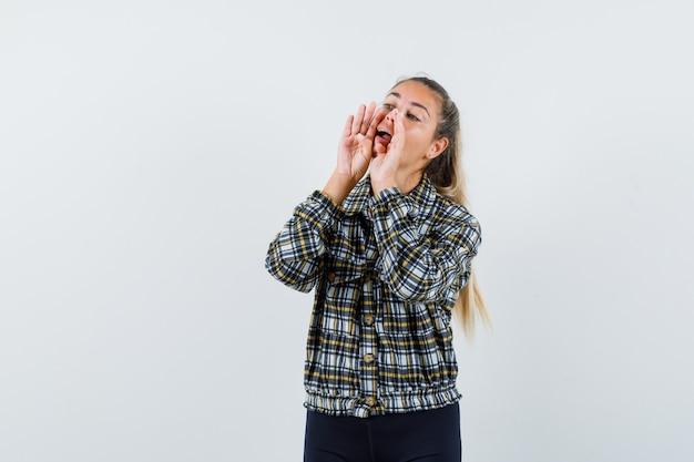 Jonge dame die iets in overhemd, korte broek, vooraanzicht schreeuwt of aankondigt.