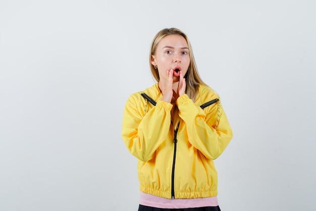 Jonge dame die iets in t-shirt, jasje schreeuwt en zelfverzekerd kijkt