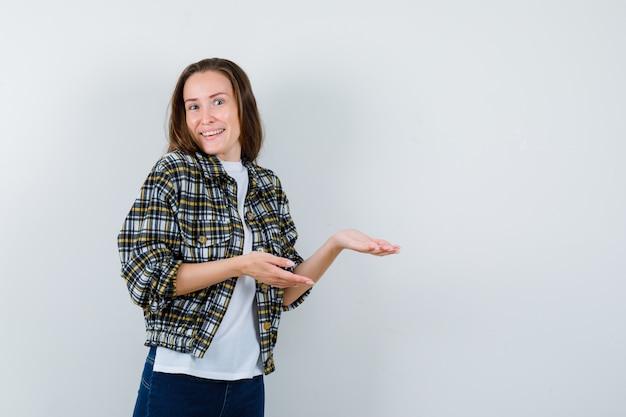 Jonge dame die iets in t-shirt, jasje, spijkerbroek verwelkomt en er vrolijk uitziet. vooraanzicht.