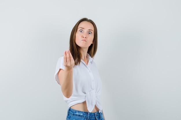 Jonge dame die iets in witte blouse probeert uit te leggen en zenuwachtig kijkt. vooraanzicht.