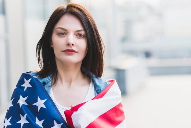Jonge dame die in amerikaanse vlag oprollen