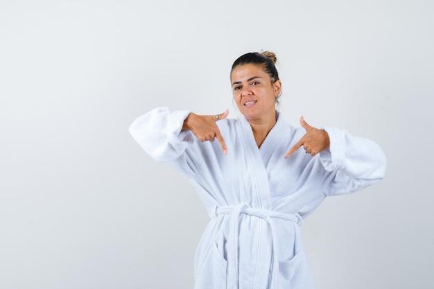 Jonge dame die in badjas naar beneden wijst en er gelukkig uitziet