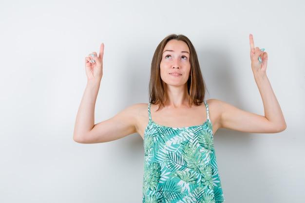 Jonge dame die in blouse omhoog wijst en er zelfverzekerd uitziet. vooraanzicht.