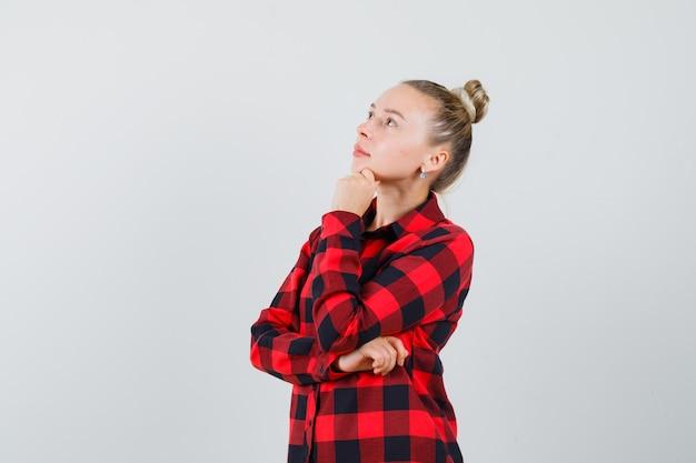 Jonge dame die in gecontroleerd overhemd met hand op kin omhoog kijkt en peinzend kijkt