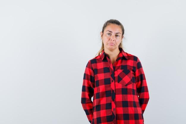 Jonge dame die in gecontroleerd overhemd voorzijde bekijkt en boos kijkt