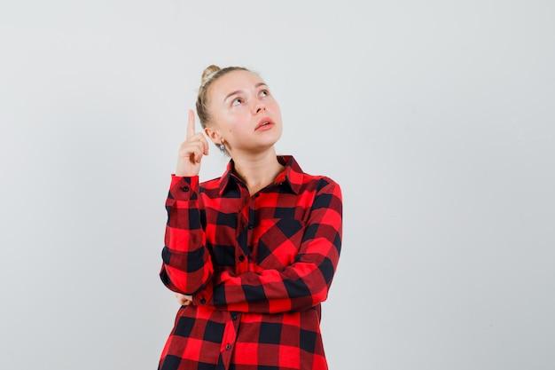 Jonge dame die in geruit overhemd benadrukt en gericht kijkt