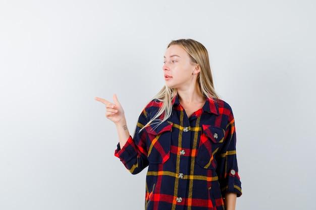Jonge dame die in geruit overhemd naar de linkerkant wijst en er zelfverzekerd uitziet. vooraanzicht.