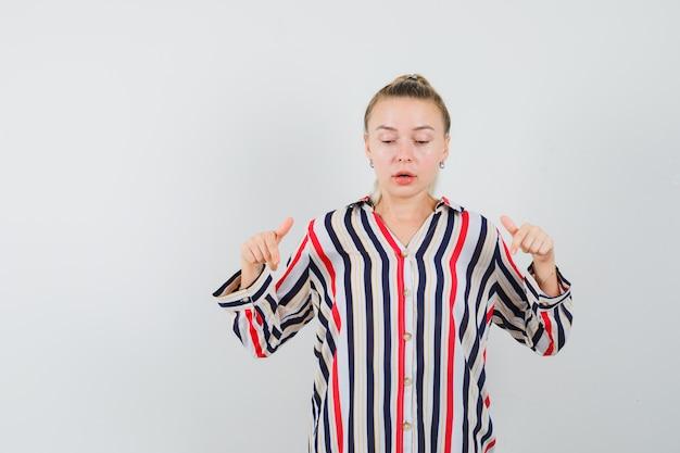 Jonge dame die in gestreept overhemd naar beneden wijst en gefocust kijkt