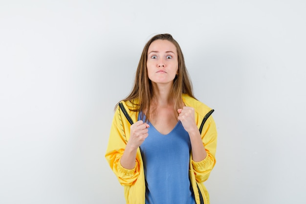 Jonge dame die in gevecht staat, poseert in t-shirt, jas en ziet er hatelijk uit.