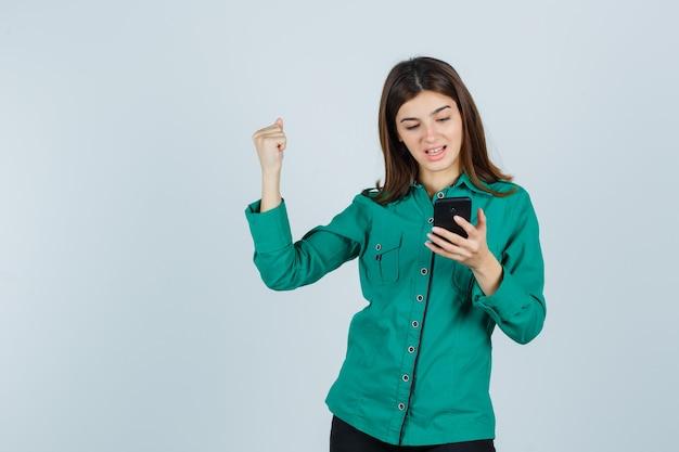 Jonge dame die in groen overhemd mobiele telefoon bekijkt, winnaargebaar toont en gelukkig, vooraanzicht kijkt.