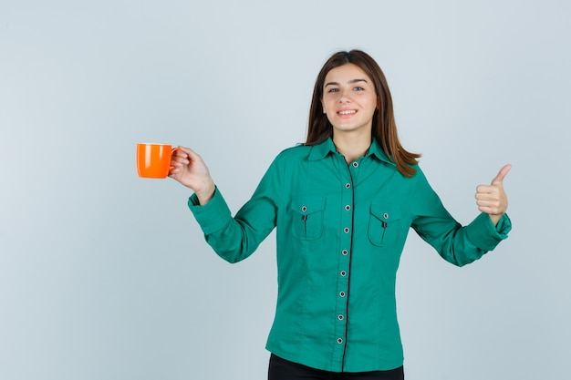 Jonge dame die in overhemd oranje kop thee houdt, duim toont en vrolijk, vooraanzicht kijkt.