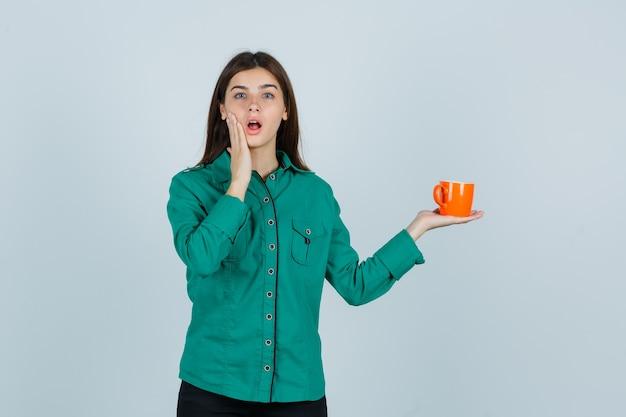 Jonge dame die in overhemd oranje kop thee houdt, hand dichtbij mond houdt en perplex, vooraanzicht kijkt.