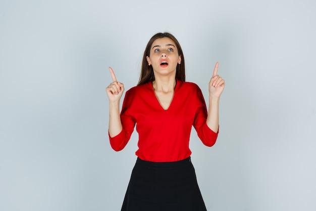 Jonge dame die in rode blouse, rok benadrukt en verbaasd kijkt