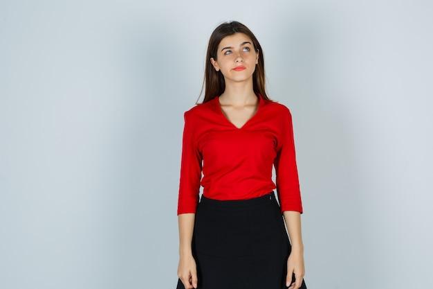 Jonge dame die in rode blouse, rok en peinzend kijkt