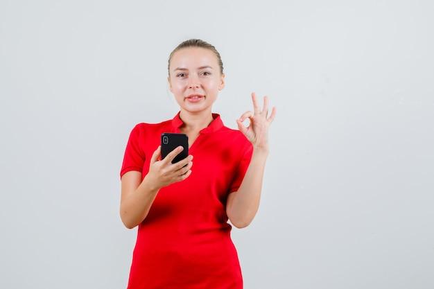 Jonge dame die in rood t-shirt mobiele telefoon met ok gebaar houdt en vrolijk kijkt
