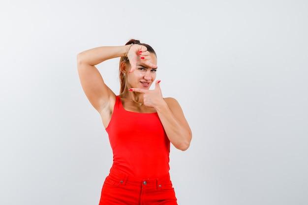 Jonge dame die kadergebaar in rood hemd, rode broek toont en er zelfverzekerd uitziet. vooraanzicht.