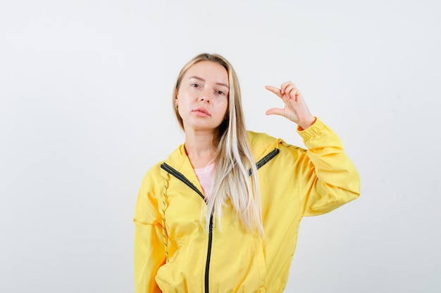 Jonge dame die klein formaatteken in t-shirt, jasje toont en er zelfverzekerd uitziet