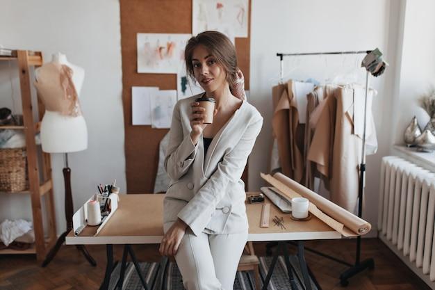Jonge dame die koffie drinkt op haar kantoor