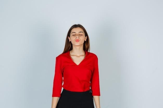 Jonge dame die kus met pruilende lippen in rode blouse, rok verzendt en er schattig uitziet