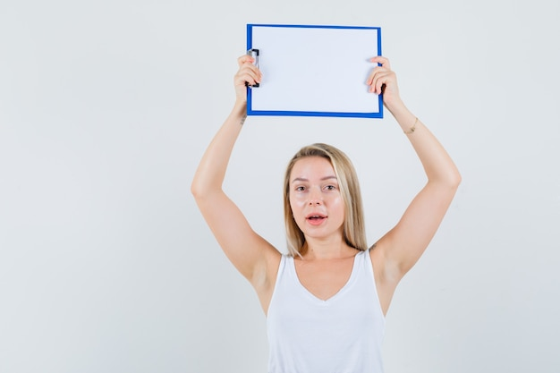 Jonge dame die leeg klembord boven haar hoofd in witte blous houdt