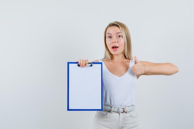 Jonge dame die leeg klembord houdt terwijl duim in witte blouse wordt getoond en er blij uitziet