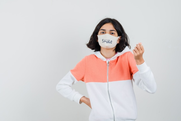 Jonge dame die liefdegebaar in hoodie, gezichtsmasker toont