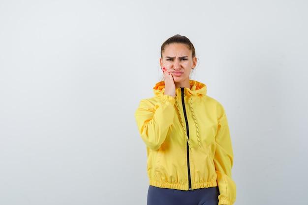 Jonge dame die lijdt aan kiespijn in gele jas en er pijnlijk uitziet, vooraanzicht.