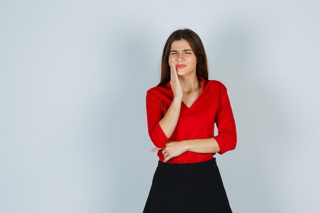 Jonge dame die lijdt aan kiespijn in rode blouse, rok en onwel kijkt