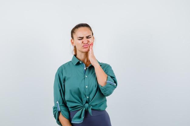 Jonge dame die lijdt aan pijnlijke kiespijn in groen shirt en er geïrriteerd uitziet. vooraanzicht.