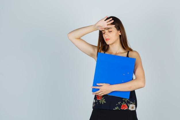 Jonge dame die map vasthoudt terwijl ze hoofdpijn heeft in blouse, rok en er moe uitziet. vooraanzicht.