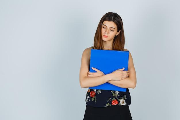 Jonge dame die map vasthoudt terwijl ze naar beneden kijkt in blouse, rok en er somber uitziet. vooraanzicht.