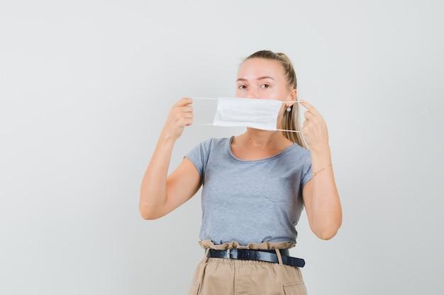 Jonge dame die medisch masker in t-shirt en broek draagt en voorzichtig kijkt