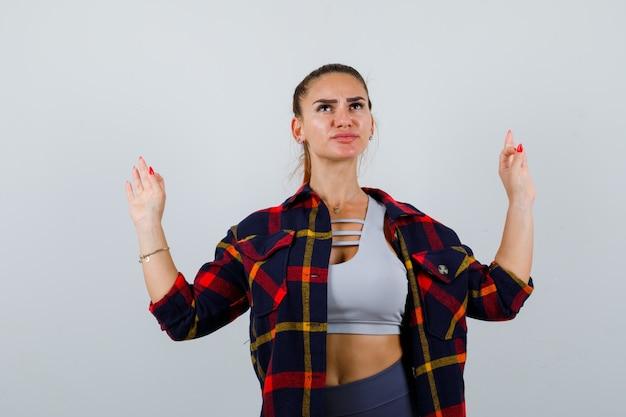 Jonge dame die meditatiegebaar in bovenkant, plaidoverhemd toont en zorgvuldig kijkt. vooraanzicht.