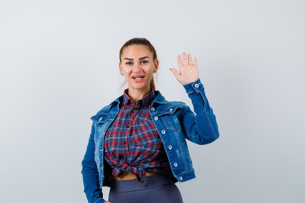 Jonge dame die met de hand zwaait voor begroeting in shirt, jas en zich afvraagt. vooraanzicht.