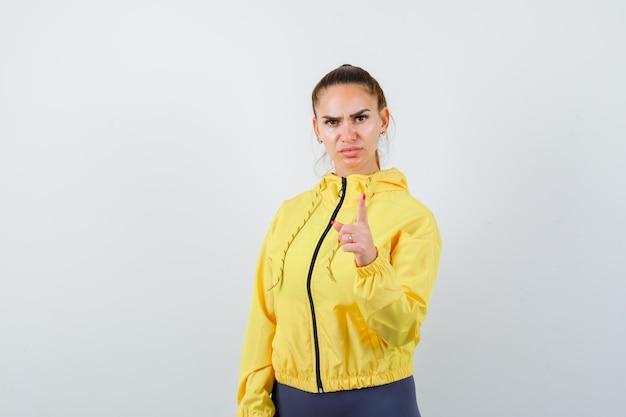 Jonge dame die met vinger in geel jasje bedreigt en ernstig kijkt. vooraanzicht.