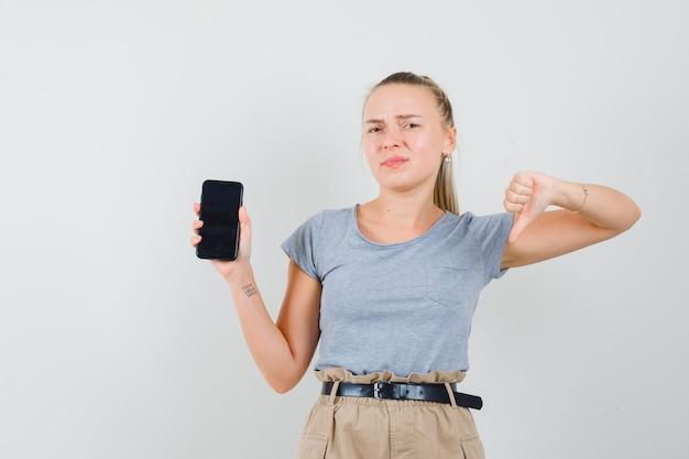 Jonge dame die mobiele telefoon houdt, duim in t-shirt en broek toont en ontevreden kijkt